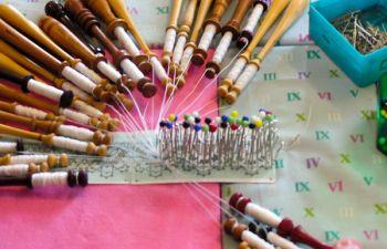 Apprendre la dentelle aux fuseaux au côté d'une dentellière